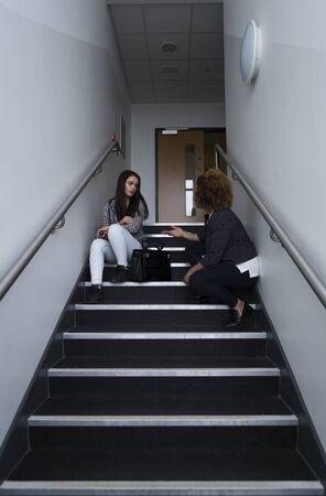 Vrouwelijke student zit op de trap in haar school, met haar leraar naast haar. Ze vertelt haar voor haar gedrag.