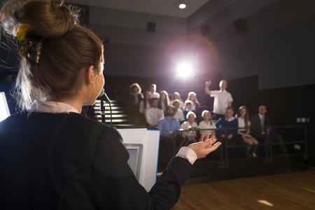 女子学生のスピーチを作るします。彼女は表彰台に立っていると、群衆の中に笑みを浮かべてします。 写真素材