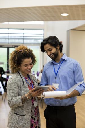 2 人の先生は、いくつかの書類と彼らの前にデジタル タブレットを保持しているし、一緒にそれを議論しています。