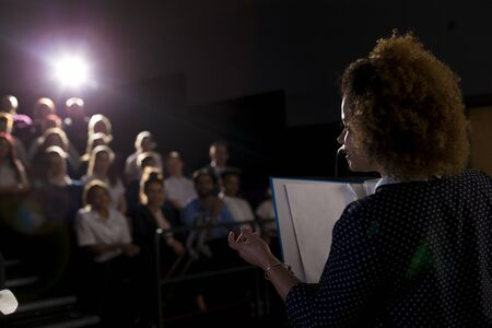 Female teacher giving a speech in a lecture hall to students and teachers.