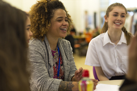 Young female teacher having a laugh with her students during lesson.