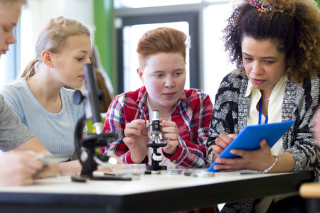 biology: Students sitting with teacher in a lesson. They are using microscopes and a digital tablet. Stock Photo