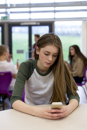 Female student sitting on her own at school. She has a smartphone in her hand which she is looking at. Stock Photo