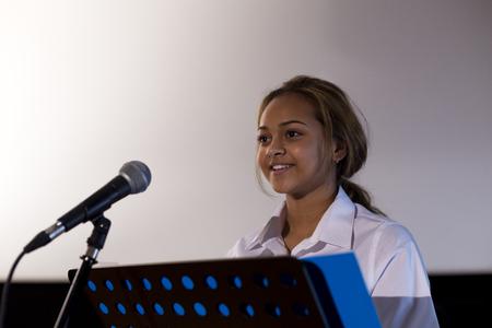 Vrouwelijke student het maken van een toespraak. Ze staat op een podium en glimlachen naar de menigte. Stockfoto
