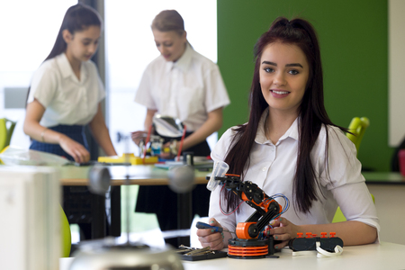talking robot: Adolescent girl in a design and technology lesson. She is smiling at the camera with a robotic arm that she is building infront of her.