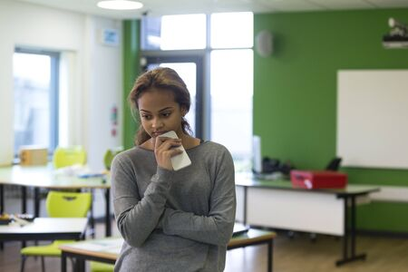 girl fighting: Teenage girl standing in an empty classroom with a mobile phone in her hand. She is looking sad with her arms folded.