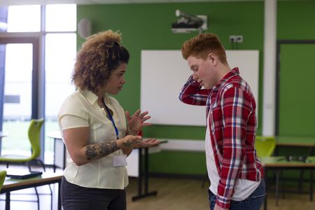 misbehaving: Teenage student being told off by his teacher at school. Stock Photo