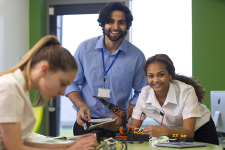 先生や生徒がロボット ・ アームを構築しながらカメラに微笑んで。別の学生は、フォア グラウンドで焦点が合っていないです。