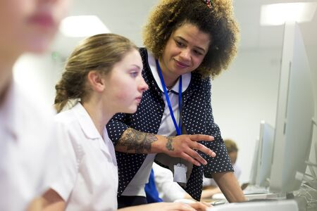 one female: Female teacher with tattoos helping one of her students, who is doing work on a computer.