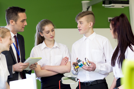 lead sled: Group of students having a discussion with their teacher about something they have built in their Design and Technology lesson. Stock Photo