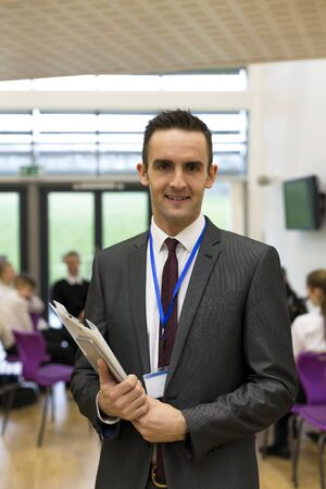 waist up: Waist up portrait of a school teacher. He is holding some paperwork and a digital tablet.