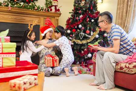 Chinese family enjoying Christmas in their home. The children are cuddling their Mother who is sitting by the Christmas tree with presents. Their father is sitting on the sofa laughing with a present in his hand.