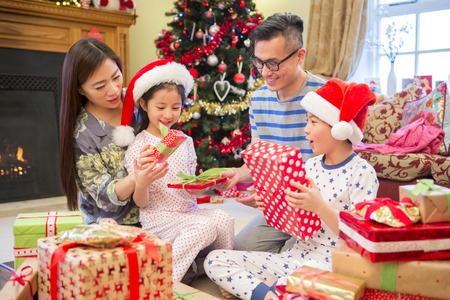 Chinese family opening presents together on Christmas morning. They are all sitting in the front room in their pyjamas, in front of the tree.