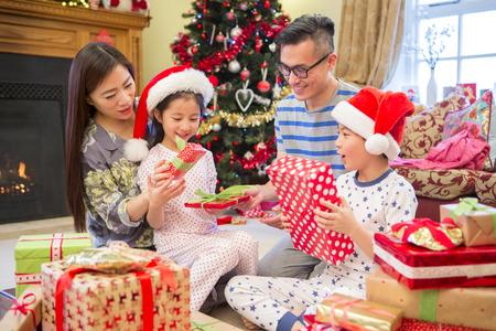 familias jovenes: apertura familia china presenta juntos en la mañana de Navidad. Todos ellos están sentados en el cuarto delantero en pijama, en frente del árbol.
