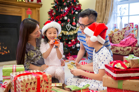 Chinese family opening their presents together on Christmas morning. they are all sitting on the floor in their living room, in front of the tree. The little girl is sitting on her Mothers knee holding up a new toy.