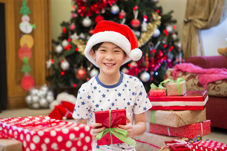 spoilt: Happy Chinese boy sitting on the floor in his living room at Christmas time. He is surrounded by presents, one of which he is holding with a big smile on his face.