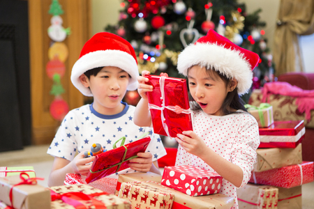 Chinese siblings sitting together on the floor in their living room on Christmas morning. They are opening presents with excited and curious expressions on their faces. Stock Photo