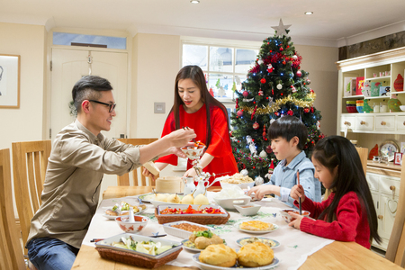 Chinese family enjoying their ~christmas dinner. They are eating traditional Chinese food. The parents are serving it round the table.