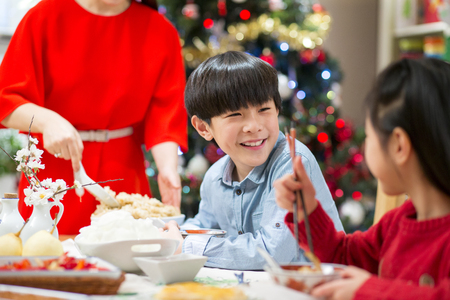 he   my sister: Chinese boy enjoying his Christmas dinner with his family. He is sharing a giggle with his sister.