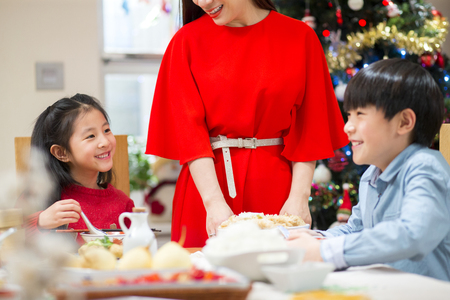 Chinese family having Christmas Dinner. The mother is standing up, dishing food to everyone. The children are laughing together. Stock Photo
