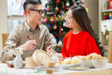 Chinese couple enjoying Christmas dinner together. They are sitting at the dining table, using chopsticks to eat chinese food. Stock Photo