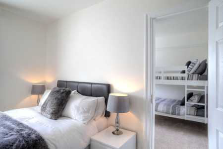 room to let: Empty hotel room with a double bed. Bunkbeds can be seen in the other room through the door. Stock Photo