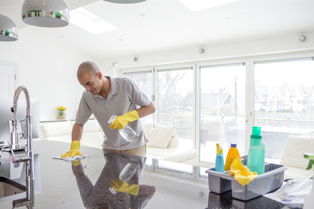 Shot of a young mixed race man cleaning a kitchen top. The kitchen is an open planned and spacious.