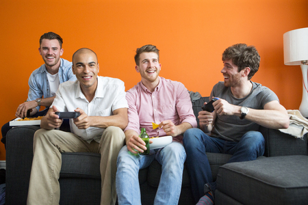 Group of men are having fun at home, playing video games. Foto de archivo