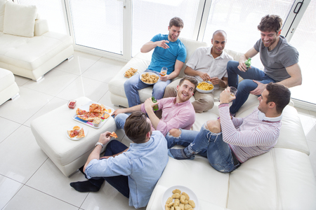 Group of men sat at home enjoying pizza and beer. Stock Photo