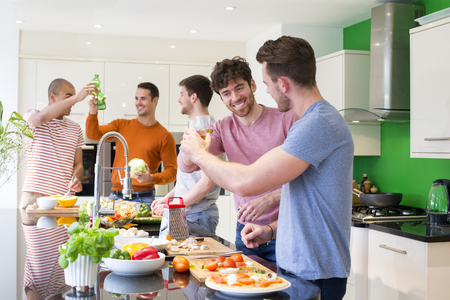 A gorup of male friends are preparing food in a kitchen, they are all having a drink and toasting.