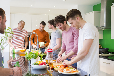 A group of men are preparing a meal together in the kitchen. Banco de Imagens