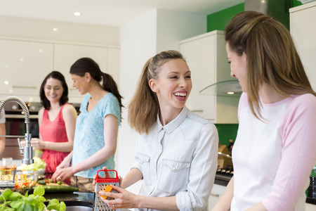 A group of women are preparing a meal together in the kitchen.
