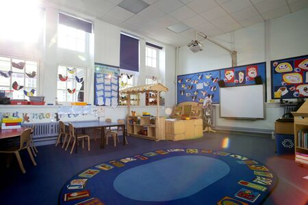 Landscape image of an empty, nursery classroom. there is a rug in the middle of the room. Stock Photo