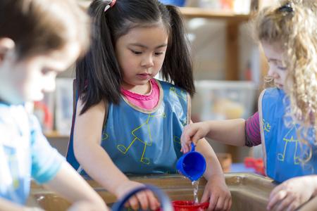 앞치마를 입고 어린 아이들은 보육원에서 함께 물 테이블과 놀고있다. 스톡 콘텐츠