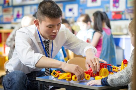 Nursery teacher is helping one of his students to make a car with building blocks. Stock Photo