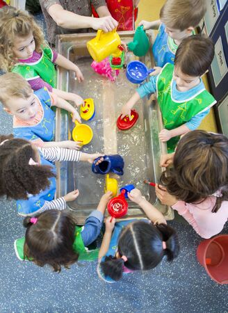 Overhead view of a class of nursery children playing at a water table. They are all wearing aprons and using plastic toys.
