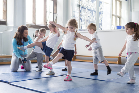 Nursery teacher helping one of her students during a physical education lesson. Stock Photo