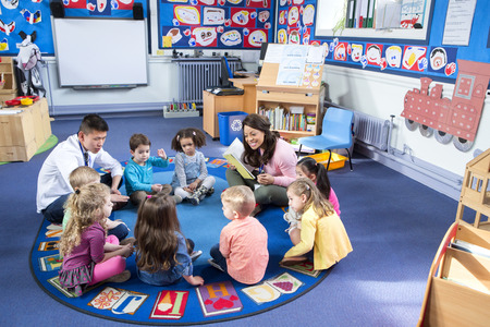 Grupo de niños de la guardería que se sientan en el suelo en su clase con sus profesores. La maestra es la lectura de un libro.