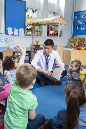 children are being read a story in nursery by a male teacher. One child has his hand up and the teacher is talking to him. Stockfoto