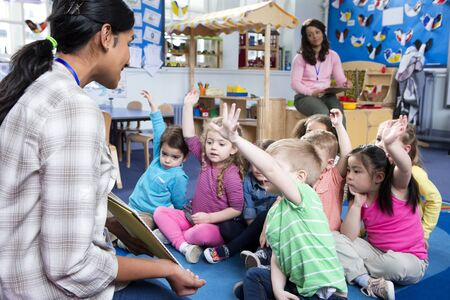 preschool children: Female teacher giving a lesson to nursery students. They are sitting on the floor and some have their hands up to ask a question.