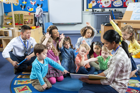 Female teacher giving a lesson to nursery students. They are sitting on the floor and some have their hands up to ask a question.
