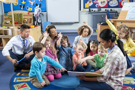 Vrouwelijke leraar die een les aan het kinderdagverblijf studenten. Ze zitten op de vloer en sommige hebben hun handen omhoog om een ??vraag te stellen. Stockfoto - 60481879