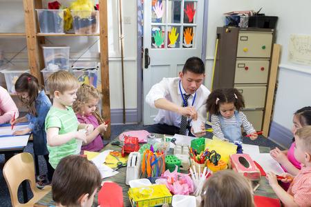Mannelijke leraar met een klas vol kwekerij studenten. Ze zijn allemaal zaten aan tafels met behulp van kunst en kunstnijverheid.