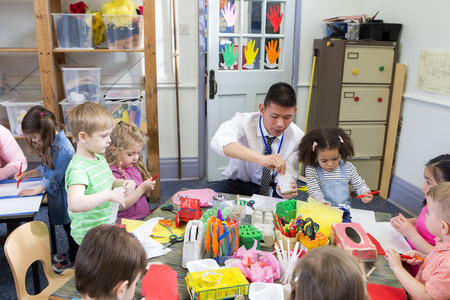 Male teacher with a class full of nursery students. They are all sat at tables using arts and crafts.