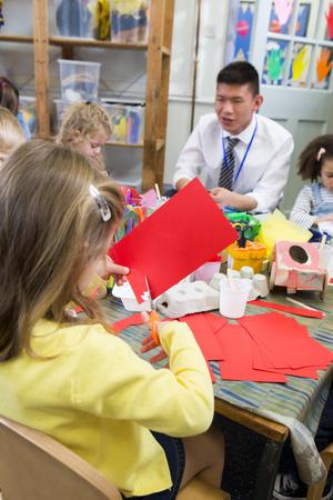niños reciclando: Niña que usa las tijeras para cortar las formas de un pedazo de papel rojo. Ella está en una clase de la guardería con otros estudiantes y un profesor.
