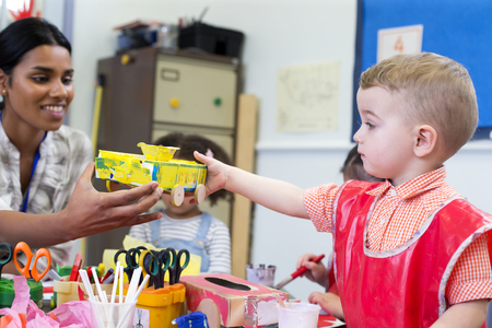 cereal box: Little boy in nursery showing his teacher the cereal box car he has made. Stock Photo