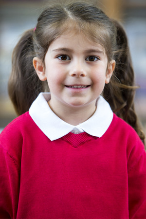 Portrait of a school girl. She is wearing a red jumper and smiling at the camera. Stock Photo