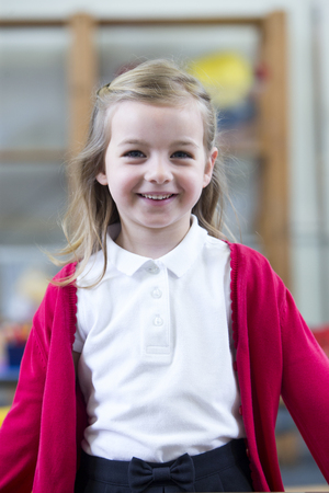 red cardigan: Portrait of a school girl. She is wearing a red cardigan and smiling at the camera.