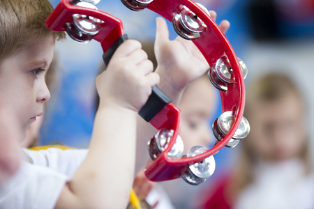 Close up of a little boy playing with a tambourine at school.