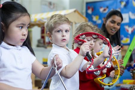 Dětské děti hrají s hudebními nástroji ve třídě. Jeden malý chlapec se dívá na kameru s tamburinou.